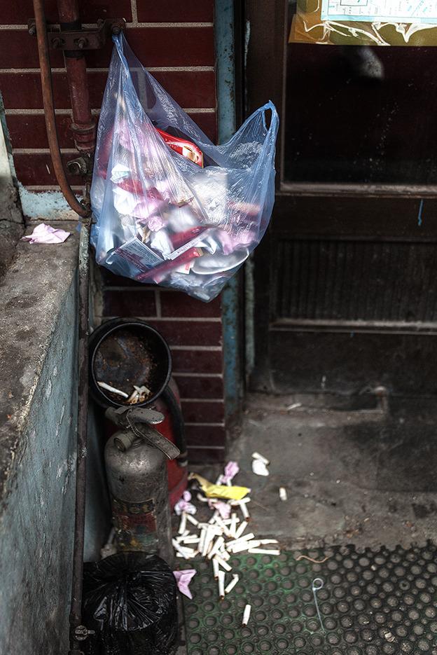 위로는 쓰레기가담긴 비닐봉투가 보이고 그 밑으로는 엎어진 재떨이가 보이며 밑으로는 나둥굴고 있는 꽁초가 보인다.